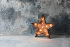 Grande rétro étoile décorative avec un bon nombre de lumières brûlantes sur le fond concret grunge Beau décor, conception moderne Photographie stock libre de droits