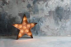 Grande rétro étoile décorative avec un bon nombre de lumières brûlantes sur le fond concret grunge Beau décor, conception moderne Photos libres de droits