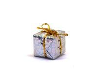 Grande regalo d'argento su fondo bianco Contenitore di regalo di Natale in fogliame che si avvolge con l'arco del filo dell'oro Fotografie Stock Libere da Diritti
