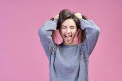 Grande retrato detalhado do estúdio na menina caucasiano nova em uma camiseta cinzenta, olhos fechados do fundo cor-de-rosa foto de stock