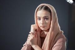 Grande ritratto emozionale di bella ragazza in un foulard rosa tricottato nello studio su un fondo grigio Fotografia Stock