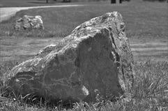 Grande roccia in bianco e nero con seconda roccia lungo una strada fotografia stock
