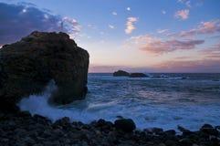 Grande roccia con le onde durante il tramonto immagine stock