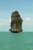 Grande roccia in mezzo del mare e di belle nubi Fotografia Stock