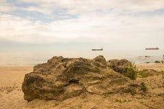 Grande roccia sulla spiaggia con il cielo nuvoloso, il mare blu e le navi da carico Fotografia Stock