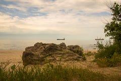 Grande roccia sulla spiaggia con il cielo nuvoloso, il mare blu e le navi da carico Immagine Stock