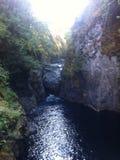 Grande rocha prendida na fenda do rio Imagem de Stock