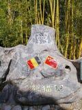 Grande roche avec les drapeaux chinois et belges à l'entrée du complexe de panda géant dans Pairi Daiza image stock