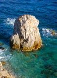 Grande roche qui émerge de la mer cristalline Photos stock