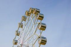 Grande roue avec les cabines rondes jaunes contre le ciel bleu en été Images libres de droits