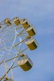 Grande roue avec les cabines rondes jaunes contre le ciel bleu en été Photos stock