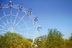 Grande roue contre le ciel bleu et les arbres Photo stock