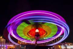 Grande roue dans le mouvement en parc d'attractions la nuit Images stock