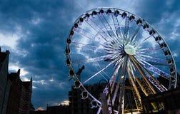 Grande roue de ferris lumineuse devant le ciel dramatique bleu-foncé images stock