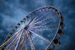 Grande roue de ferris lumineuse devant le ciel dramatique bleu-foncé image stock