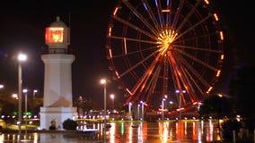 Grande roue et phare en parc de miracle la nuit sur le remblai de Batumi banque de vidéos