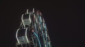 Grande roue tournant au parc d'attractions sous le ciel nocturne foncé clips vidéos