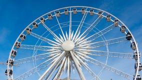 Grande roue tournant sur le fond de ciel bleu Photo stock
