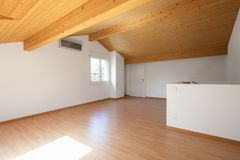 Grande sótão com assoalhos de madeira e feixes expostos foto de stock