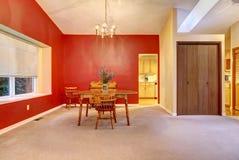 Grande sala de jantar com parede vermelha e a tabela de madeira pequena. Imagens de Stock Royalty Free