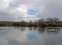 Grande salgueiro da brisa do vidoeiro de rio da água na reflexão do céu nebuloso da costa Fotos de Stock Royalty Free