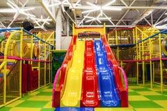 Grande salle de jeux du ` s d'enfants avec une glissière et boules colorées au centre de divertissement photos stock