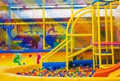 Grande salle de jeux du ` s d'enfants avec une glissière et boules colorées au centre de divertissement image libre de droits