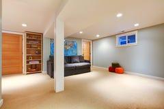 Grande salle de séjour bleue de sous-sol avec le sofa. photographie stock libre de droits