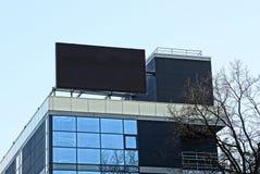 Grande schermo nero sul tetto di una casa alta con le finestre sui precedenti del cielo Immagini Stock Libere da Diritti