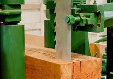 Grande scie à ruban coupant un bois de construction Photo stock