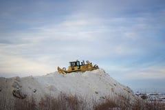 Grande selezionatore del trattore che spinge e che accatasta neve su una collina enorme della neve fotografie stock libere da diritti