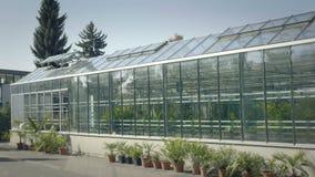 Grande serra con le pareti di vetro, fondamenti, tetto di timpano, letto del giardino archivi video
