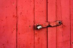Grande serratura del ferro che appende su una porta dipinta rossa fotografia stock