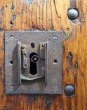 Grande serrure rouillée carrée de fer avec le trou de la serrure dans une vieille porte en bois vernie avec l'extrémité des rivet images stock