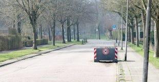 Grande servizio della piantatrice come blocco stradale, applicante il limite di velocità di 30km/h fotografie stock