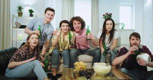 Grande società concentrata e carismatica di multi etnico degli amici davanti alla TV in salone essi a di sorveglianza archivi video