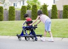 Grande soeur aidant le frère handicapé dans le marcheur Images libres de droits