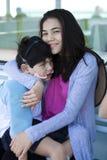 Grande soeur prenant soin de petit frère handicapé Photo libre de droits
