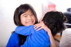 Grande soeur tenant son petit frère handicapé Images libres de droits