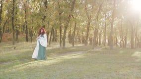 Grande sorcière potelée mignonne rousse dans les rayons des appels de coucher du soleil pour des lutins et de peu d'edbfov vert p banque de vidéos