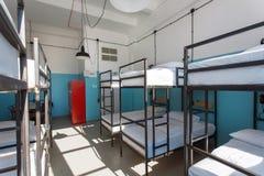 Grande spazio della camera da letto degli studenti senza gente dentro un ostello per i viaggiatori con zaino e sacco a pelo ed il Immagini Stock