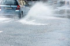 Grande spruzza di acqua piovana dalle ruote di automobile durante la pioggia persistente Immagini Stock