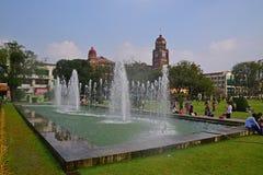 Grande stagno della fontana in Maha Bandula Garden con la precedente costruzione dell'alta corte Immagine Stock Libera da Diritti