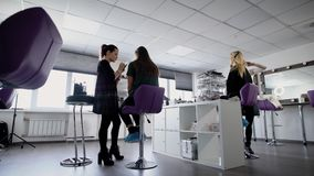 Grande stanza accogliente Negozio di bellezza Lavoro dei truccatori sulle immagini dei clienti Contro lo sfondo di grandi finestr archivi video