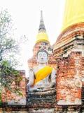 Grande statua bianca di Buddha che indossa un cappotto e una pagoda gialli con luce solare a Wat Yai Chaimongkol, si Ayutthaya, T fotografia stock