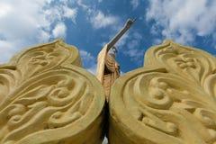 Grande statua dorata diritta di Buddha nel punto la sua posizione del dito immagine stock