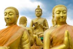 Grande statue d'or de Bouddha entourant par de petites statues de Bouddha Images libres de droits