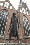 Grande statue placée devant une vieille église néerlandaise photos stock