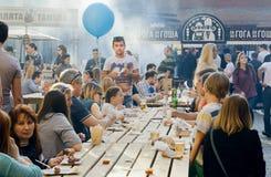 Grande table extérieure avec les personnes de consommation et potables pendant le festival populaire de nourriture de rue Photo libre de droits