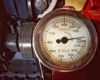 Grande tacômetro velho do metal com um calibre redondo com o seletor marcado nos números montados em um grande motor foto de stock royalty free